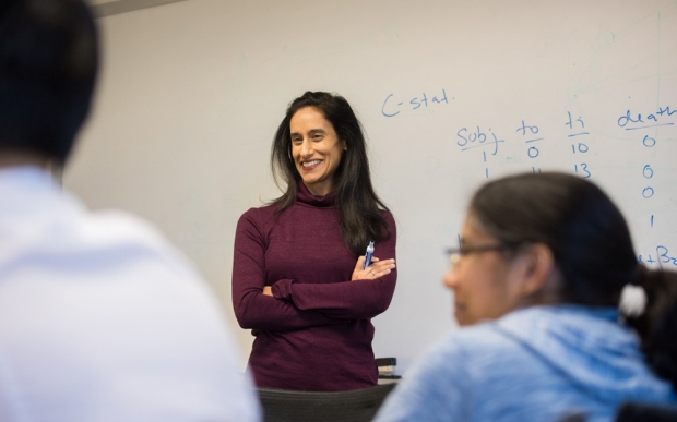 Manisha Desai standing before whiteboard and smiling at group of students